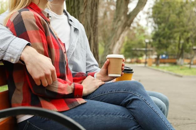 Casal sentado no parque tomando café Foto Premium