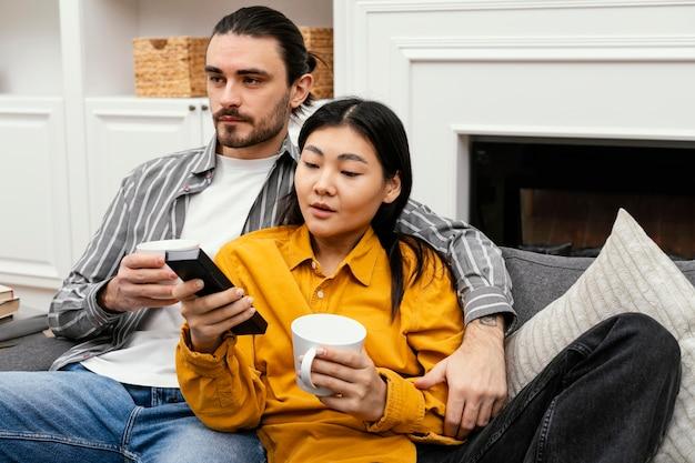 Casal sentado no sofá assistindo tv Foto gratuita