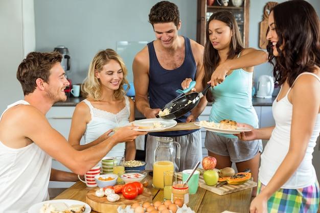 Casal servindo café da manhã para os amigos na mesa Foto Premium