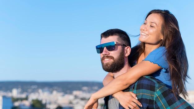 Casal sorridente ao ar livre na cidade com espaço de cópia Foto gratuita