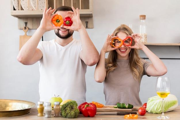 Casal sorridente brincando com pimentão Foto gratuita