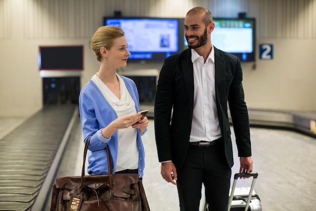 Casal sorridente caminhando com suas sacolas Foto gratuita