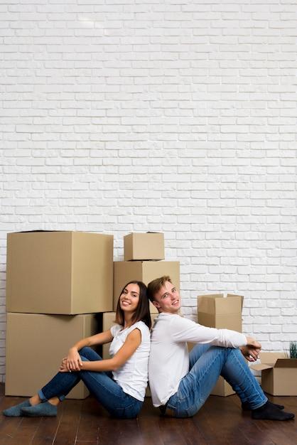 Casal sorridente com caixas e cópia-espaço Foto Premium