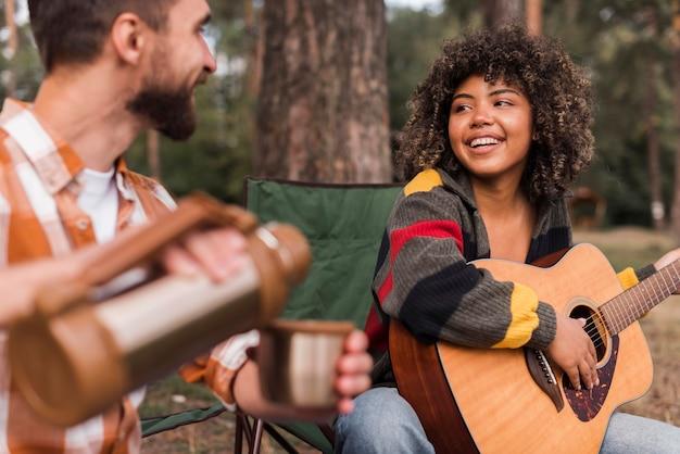 Casal sorridente curtindo acampar ao ar livre com violão e bebida quente Foto gratuita