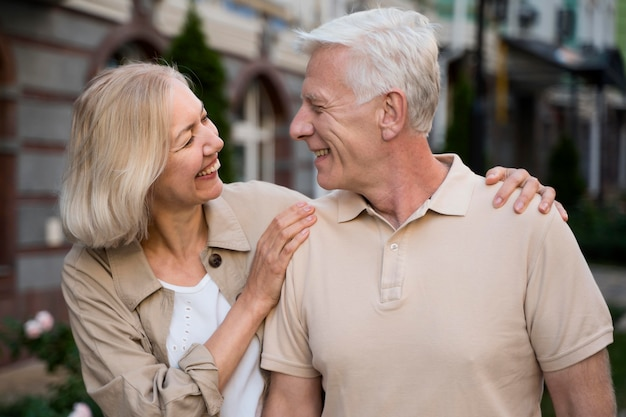 Casal sorridente de idosos caminhando juntos pela cidade Foto gratuita