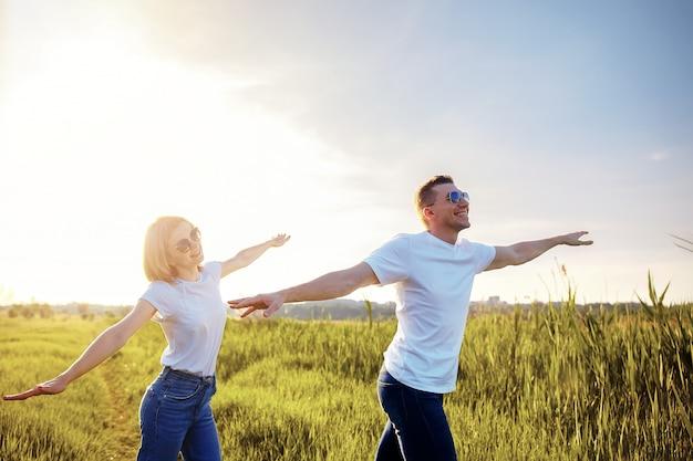 Casal sorridente em camisetas brancas, óculos escuros e jeans espalhados braços imitando aviões Foto Premium