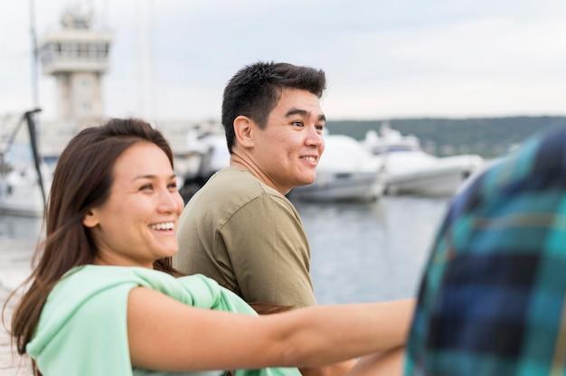 Casal sorridente encontrando seus amigos ao ar livre Foto gratuita