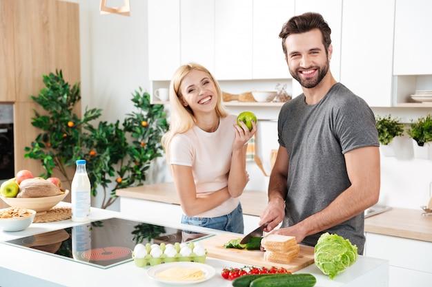Casal sorridente, passar algum tempo juntos na cozinha Foto gratuita