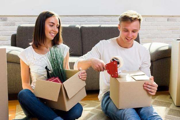 Casal sorridente pulando caixas de papelão Foto gratuita
