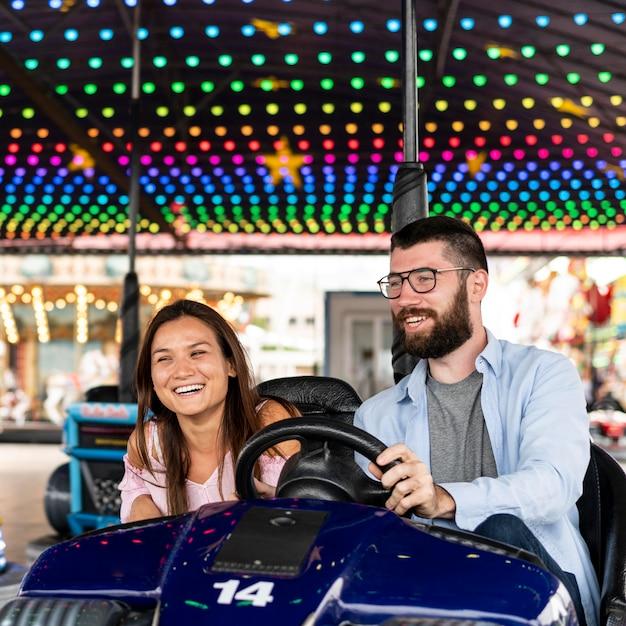 Casal sorridente se divertindo com carrinhos de choque Foto gratuita
