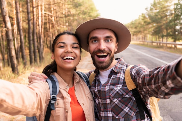 Casal sorridente tirando uma selfie enquanto viaja Foto gratuita
