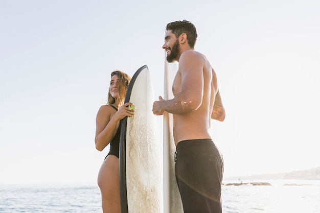 Casal surfista na praia Foto gratuita
