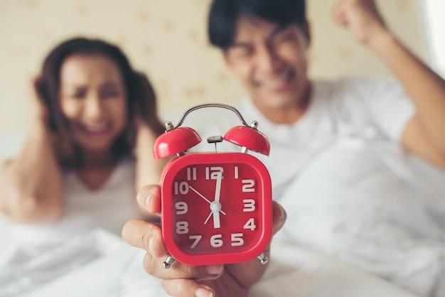 Casal tendo problemas em acordar cedo de manhã na cama Foto gratuita