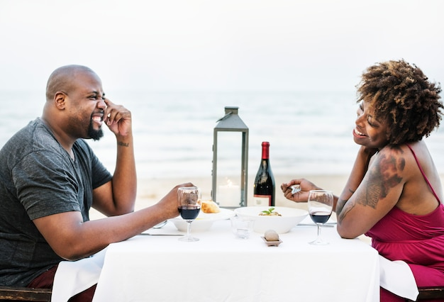 Casal tendo um jantar romântico na praia Foto Premium
