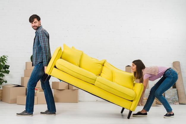 Casal tentando colocar o sofá amarelo em sua nova casa Foto gratuita