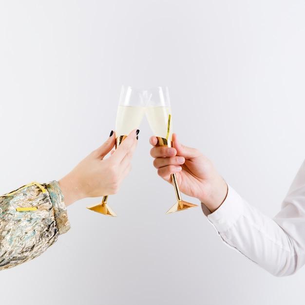 Casal tilintando copos de vinho espumante Foto gratuita