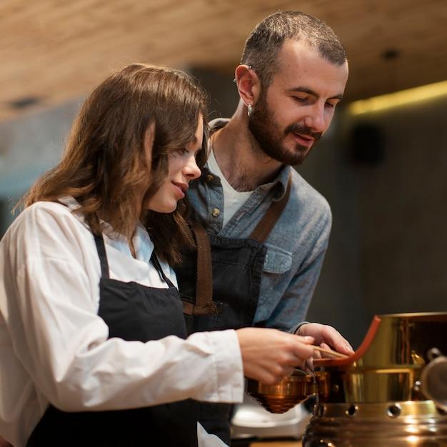 Casal trabalhando na máquina de café Foto gratuita