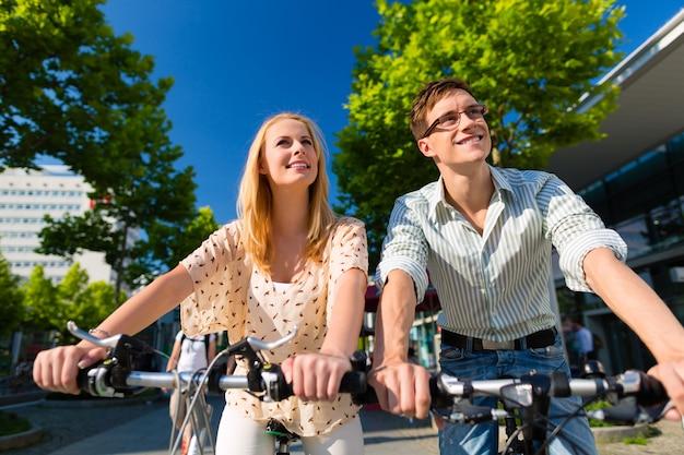 Casal urbano andando de bicicleta em tempo livre na cidade Foto Premium