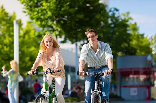 Casal urbano andando de bicicleta no tempo livre na cidade Foto Premium