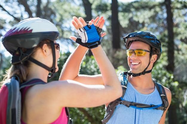 Casal usando capacete dando cinco durante a aventura Foto Premium