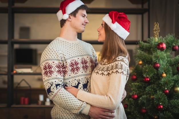 Casal usando chapéus de papai noel, abraçando um ao outro Foto gratuita