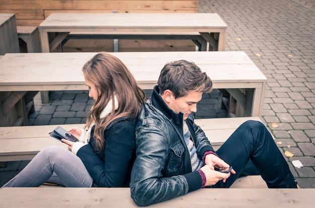 Casal usando telefone móvel esperto na fase comum moderna de desinteresse mútuo Foto Premium
