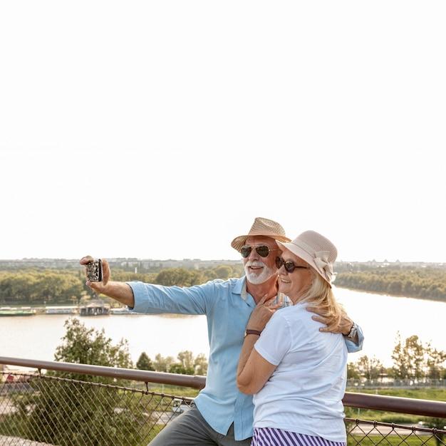 Casal velho feliz tomando uma selfie Foto gratuita