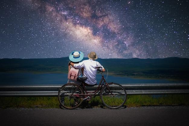 casal-viajante-sentado-perto-de-uma-bicicleta-e-olhando-para-a-via-lactea-e-estrelas-no-ceu_45381-287.jpg