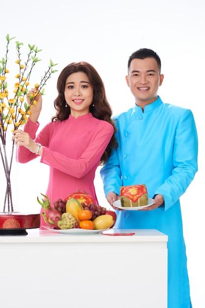 Casal vietnamita em roupas tradicionais brilhantes, posando no estúdio com frutas e flores Foto gratuita
