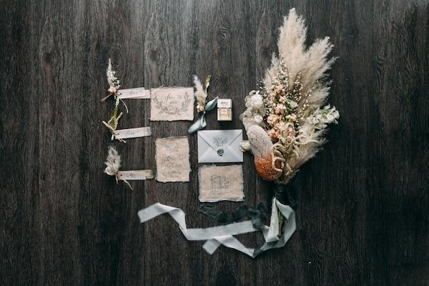 Casamento buquê artes rústicas e gráficas de cartões de caligrafia linda com bobinas de flores e chiffon na mesa de madeira. convite de casamento lindo. vista do topo. Foto Premium