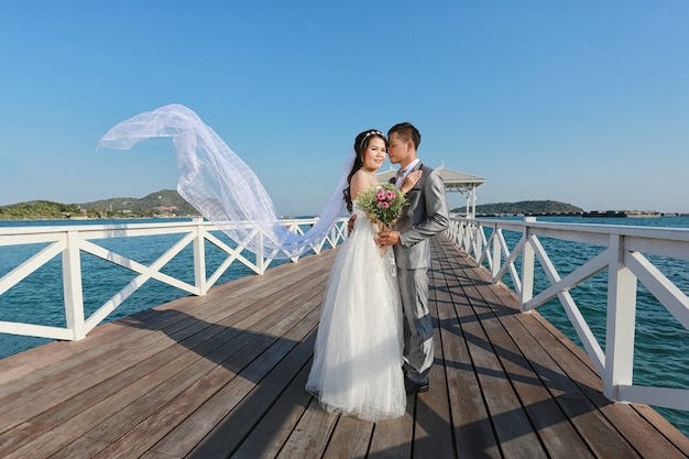 Casamentos tailandeses da fotografia do pre em uma ponte de madeira de atsadang Foto Premium