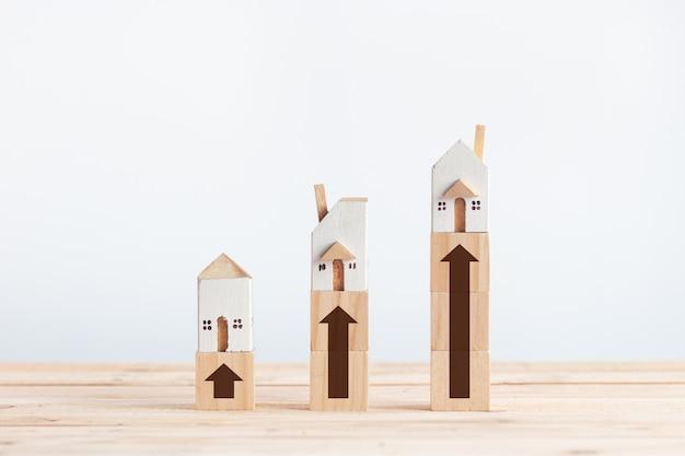 Casas brancas em miniatura no bloco de madeira com sinal de seta de crescimento Foto Premium