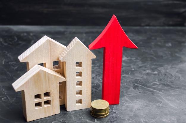 Casas de madeira com uma seta vermelha para cima. conceito de alta demanda por imóveis. Foto Premium