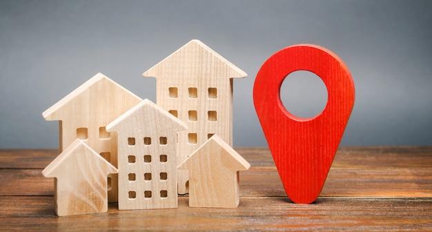 Casas de madeira em miniatura e um marcador de geolocalização. localização de edifícios residenciais. Foto Premium