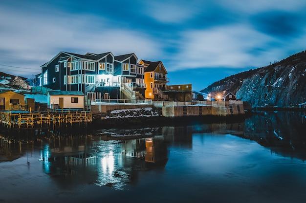 Casas perto do corpo de água durante a noite Foto gratuita