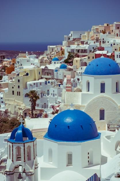 Casas tradicionais e famosas e igrejas com cúpulas azuis sobre a caldeira, mar egeu Foto Premium