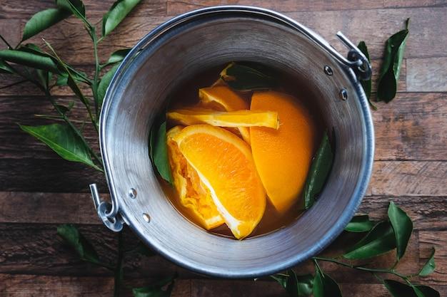 Casca de laranja e suco de laranja em um balde Foto Premium
