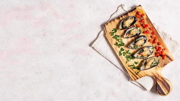 Cascas de mexilhão saboroso em uma placa de madeira Foto gratuita