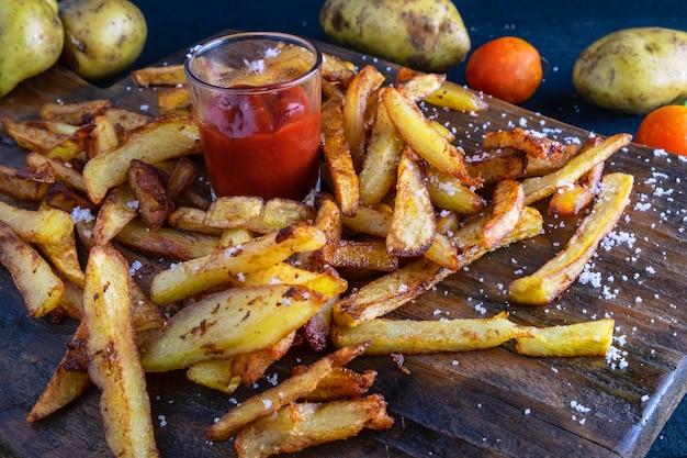 Caseiro batata frita com ketchup na terra traseira de madeira Foto Premium