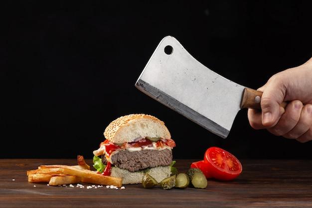 Caseiro hambúrguer cortado ao meio close-up com carne, tomate, alface, queijo e batata frita na madeira Foto Premium