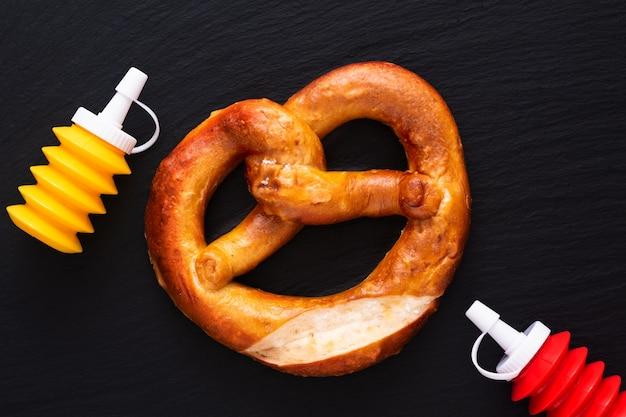 Caseiro nó torcido pretzels de sal macio no fundo da placa de ardósia preta Foto Premium