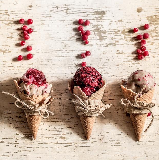 Casquinha de sorvete waffle com frutas no fundo de madeira Foto gratuita