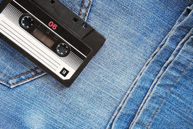 Cassete áudio retro do vintage da calças de ganga, close-up. tecnologias de mídia dos últimos 80 s. quadro conceptual para ilustrar as memórias do passado. a vista do topo. Foto Premium