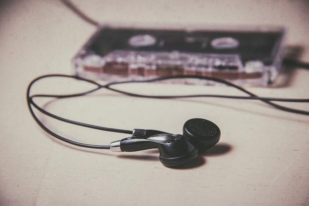Cassete de áudio magnético vintage e fones de ouvido no chão de madeira Foto Premium