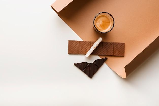 Castanho; barra de chocolate branco e escuro com copo de café sobre papel contra o pano de fundo branco Foto gratuita