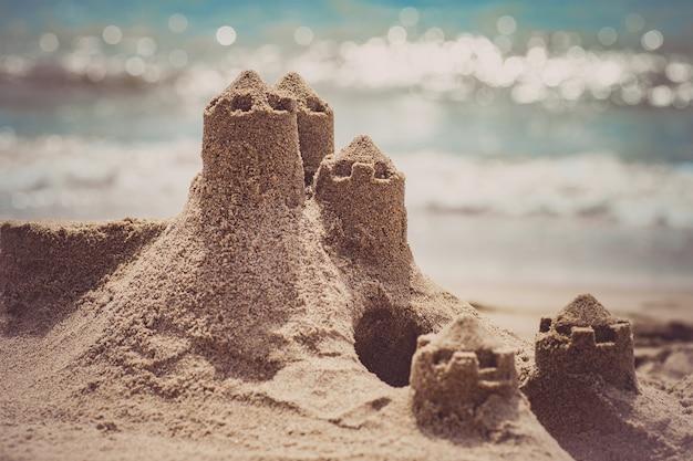 Castelo de areia em pé na praia. conceito de férias de viagens. Foto Premium