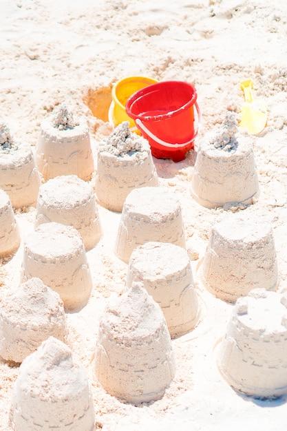 Castelo de areia na praia branca com brinquedos de crianças de plástico e fundo do mar Foto Premium