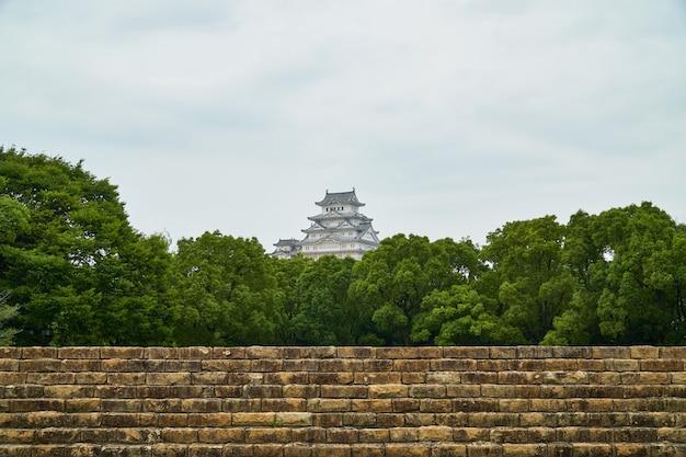Castelo de himeji com árvore e parede velha Foto Premium