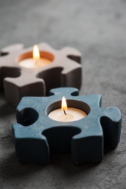 Castiçais com velas em chamas no fundo de pedra Foto Premium