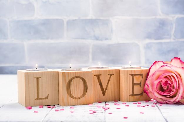 Castiçais de madeira românticos com punhos de chá ardentes. cartão de dia dos namorados Foto Premium